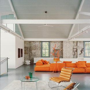 Réalisation d'un salon urbain ouvert avec un mur blanc, béton au sol, un sol gris, un plafond voûté et un mur en parement de brique.