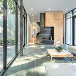 Ispirazione per un soggiorno minimal con pavimento in ardesia e camino bifacciale
