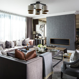 This is an example of a large traditional formal enclosed living room in London with grey walls, a hanging fireplace, a metal fireplace surround, black floors, medium hardwood flooring and no tv.