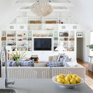 Example of a beach style open concept medium tone wood floor living room design in New York with white walls and a wall-mounted tv