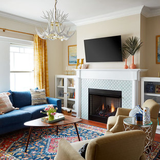 Inspiration for an eclectic living room in Chicago with beige walls, medium hardwood flooring, a standard fireplace, a tiled fireplace surround, a wall mounted tv and red floors.
