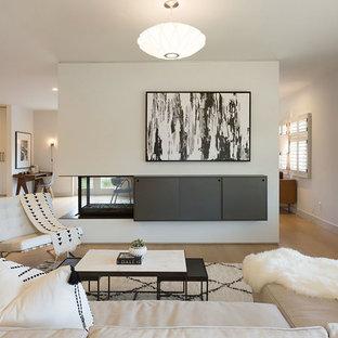 Foto di un grande soggiorno minimalista aperto con sala formale, pareti bianche, parquet chiaro, camino bifacciale, parete attrezzata e cornice del camino in metallo