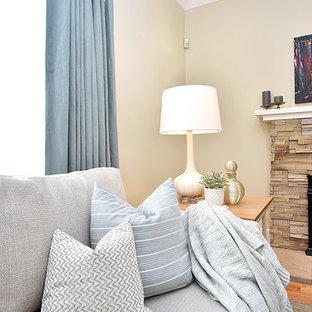 オタワの中サイズのビーチスタイルのおしゃれな独立型リビング (黄色い壁、淡色無垢フローリング、標準型暖炉、石材の暖炉まわり、壁掛け型テレビ) の写真