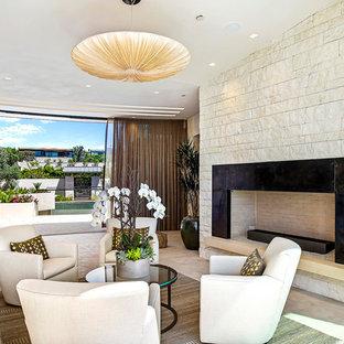 Réalisation d'un salon mansardé ou avec mezzanine design de taille moyenne avec une salle de réception, un mur beige, un sol beige, un sol en travertin, une cheminée standard, un manteau de cheminée en pierre et aucun téléviseur.