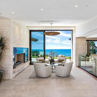 Immagine di un soggiorno minimal di medie dimensioni e stile loft con sala formale, pareti beige, pavimento in travertino, camino classico, cornice del camino in pietra, nessuna TV e pavimento beige