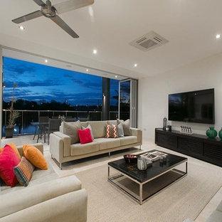 Modelo de salón abierto, moderno, grande, sin chimenea, con paredes blancas, suelo de travertino, televisor colgado en la pared y suelo multicolor