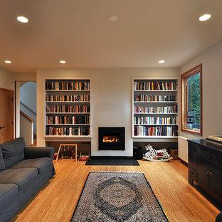 Foto på ett stort funkis allrum med öppen planlösning, med vita väggar, bambugolv, en standard öppen spis och ett bibliotek