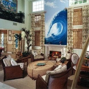 Esempio di un ampio soggiorno tropicale stile loft con pareti verdi, camino classico, cornice del camino in pietra, TV a parete e pavimento marrone