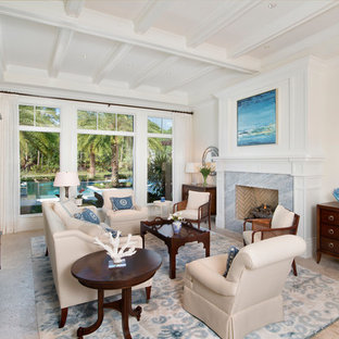 マイアミの広いトロピカルスタイルのおしゃれな独立型リビング (フォーマル、白い壁、磁器タイルの床、標準型暖炉、石材の暖炉まわり、テレビなし) の写真