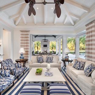 Foto di un grande soggiorno tropicale aperto con sala formale, pareti bianche, pavimento in gres porcellanato, nessun camino e nessuna TV