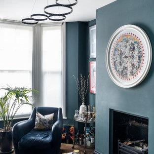 Esempio di un piccolo soggiorno bohémian chiuso con pareti blu, pavimento in legno massello medio, camino classico, cornice del camino in mattoni, nessuna TV e pavimento marrone