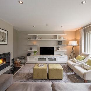 ダブリンのトランジショナルスタイルのおしゃれなLDK (グレーの壁、カーペット敷き、据え置き型テレビ、横長型暖炉) の写真