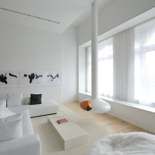 Photo of a scandinavian living room in New York with white walls, light hardwood floors and a hanging fireplace.