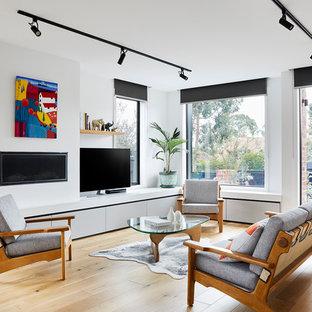 Ispirazione per un soggiorno design di medie dimensioni e aperto con parquet chiaro, cornice del camino in intonaco, TV autoportante, pareti bianche, camino lineare Ribbon e pavimento marrone