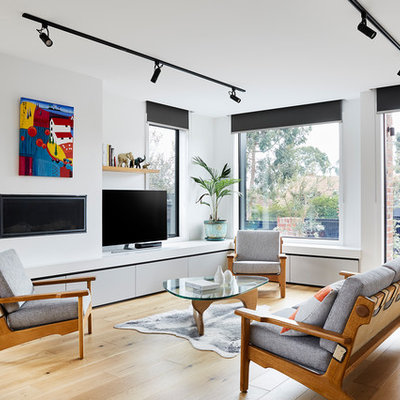 Mid-sized trendy open concept light wood floor and brown floor living room photo in Melbourne with a plaster fireplace, a tv stand, white walls and a ribbon fireplace
