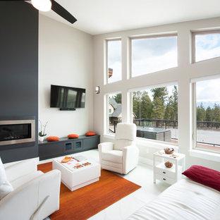 他の地域のモダンスタイルのおしゃれなLDK (白い壁、トラバーチンの床、標準型暖炉、壁掛け型テレビ、白い床) の写真