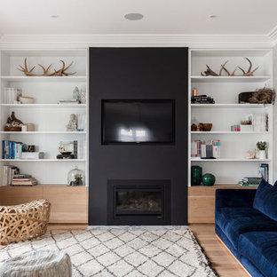 シドニーの大きいビーチスタイルのおしゃれなLDK (黒い壁、無垢フローリング、標準型暖炉、漆喰の暖炉まわり、壁掛け型テレビ、茶色い床) の写真
