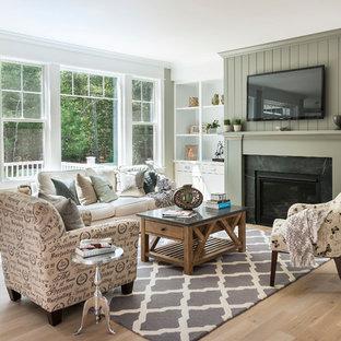 Immagine di un soggiorno country aperto con pareti verdi, parquet chiaro, camino classico, cornice del camino in pietra e TV a parete