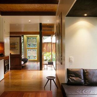 Esempio di un soggiorno tropicale di medie dimensioni con pavimento in compensato