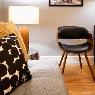 Diseño de salón para visitas cerrado, moderno, pequeño, sin chimenea, con paredes grises, suelo de madera clara, televisor independiente y suelo amarillo