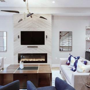 Idee per un grande soggiorno contemporaneo aperto con pareti beige, parquet chiaro, camino sospeso, cornice del camino in pietra e parete attrezzata