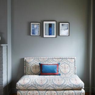 Ispirazione per un soggiorno tradizionale con pareti grigie, pavimento in legno massello medio e cornice del camino in mattoni