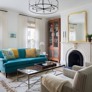 Example of a transitional formal living room design in New York with white walls, a standard fireplace and no tv