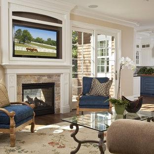 Inspiration för klassiska vardagsrum, med beige väggar, en standard öppen spis och en väggmonterad TV
