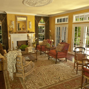 Inspiration for a timeless living room remodel in San Francisco with yellow walls and a standard fireplace