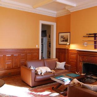 Diseño de salón para visitas cerrado, actual, grande, con parades naranjas, suelo de madera clara, chimenea tradicional y marco de chimenea de madera