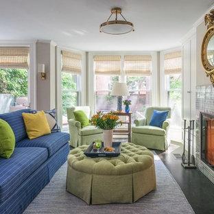 Idee per un soggiorno chic aperto con pareti beige, camino classico, cornice del camino piastrellata e pavimento nero