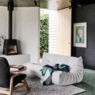 Mittelgroßes, Offenes Modernes Wohnzimmer mit weißer Wandfarbe, Betonboden, Kaminofen, Kaminumrandung aus Metall und grünem Boden