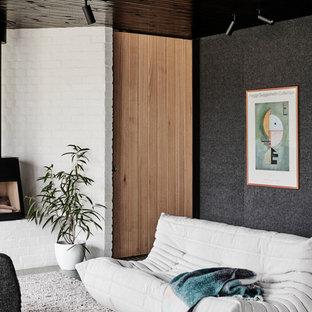 Imagen de salón abierto, moderno, de tamaño medio, con paredes blancas, suelo de cemento, estufa de leña, marco de chimenea de metal y suelo verde