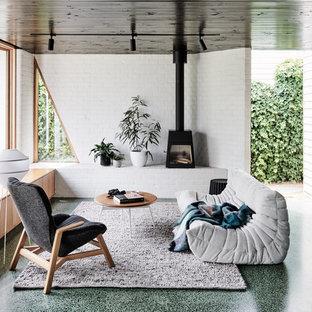 Foto på ett mellanstort funkis allrum med öppen planlösning, med betonggolv, en öppen vedspis, en spiselkrans i metall, grönt golv och vita väggar