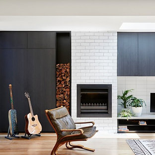 Contemporary living room in Melbourne with white walls, medium hardwood floors, a standard fireplace, a brick fireplace surround and brown floor.