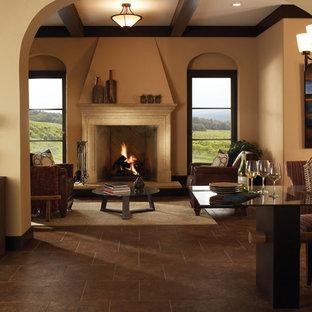 サクラメントの大きい地中海スタイルのおしゃれなLDK (フォーマル、ベージュの壁、磁器タイルの床、標準型暖炉、石材の暖炉まわり、テレビなし、茶色い床) の写真