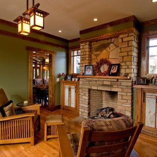 他の地域のトラディショナルスタイルのおしゃれな独立型リビング (緑の壁、無垢フローリング、標準型暖炉、石材の暖炉まわり) の写真