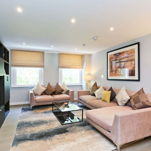 Design ideas for a traditional living room in London with white walls, light hardwood flooring, a freestanding tv and beige floors.