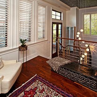 Ejemplo de salón para visitas tipo loft, urbano, pequeño, sin chimenea y televisor, con paredes blancas, suelo de madera oscura y suelo rojo