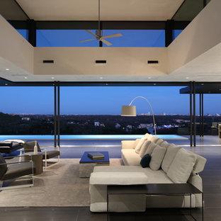 オースティンの大きいコンテンポラリースタイルのおしゃれなLDK (白い壁、磁器タイルの床、吊り下げ式暖炉、タイルの暖炉まわり、壁掛け型テレビ、黒い床) の写真
