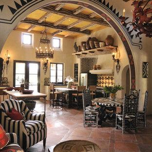 Imagen de salón abierto, de estilo americano, con paredes beige, suelo naranja y suelo de baldosas de terracota