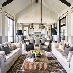Foto di un soggiorno classico aperto con pareti grigie, parquet chiaro, camino classico e cornice del camino in pietra
