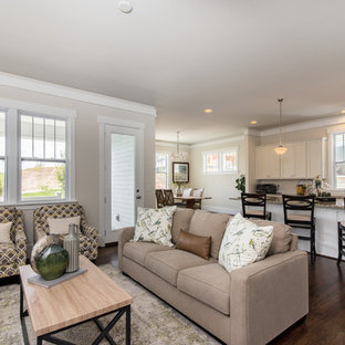 Traditional open concept living room in Charlotte with beige walls, medium hardwood floors and brown floor.