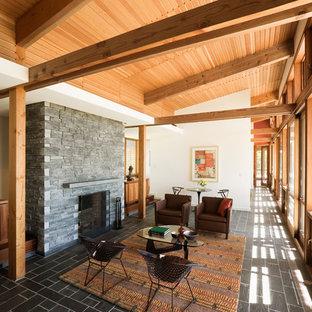 Immagine di un soggiorno minimalista aperto e di medie dimensioni con sala formale, camino classico, cornice del camino in pietra, pareti bianche, pavimento in ardesia e nessuna TV