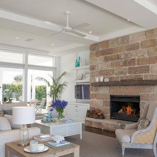 シドニーの大きいビーチスタイルのおしゃれなLDK (白い壁、濃色無垢フローリング、標準型暖炉、石材の暖炉まわり、壁掛け型テレビ) の写真