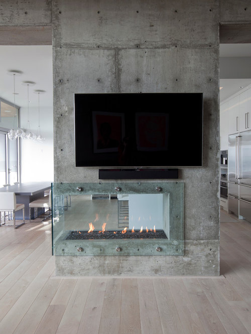 trendy living room photo in vancouver with a two sided fireplace
