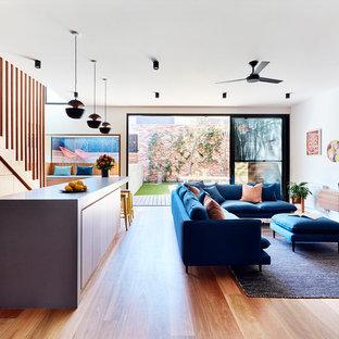 メルボルンの小さいコンテンポラリースタイルのおしゃれなLDK (無垢フローリング、両方向型暖炉、レンガの暖炉まわり、茶色い床、白い壁、壁掛け型テレビ) の写真