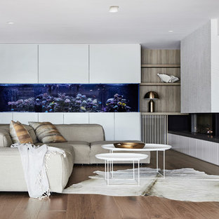 This is an example of a large contemporary open concept living room in Sydney with white walls, medium hardwood floors, a wall-mounted tv, brown floor, a standard fireplace and a tile fireplace surround.