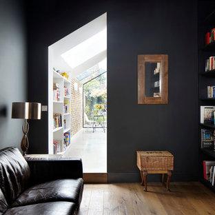 ロンドンの小さいコンテンポラリースタイルのおしゃれな独立型リビング (ライブラリー、黒い壁、濃色無垢フローリング、暖炉なし、埋込式メディアウォール) の写真