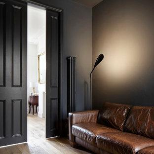 Foto de biblioteca en casa cerrada, contemporánea, pequeña, sin chimenea, con paredes negras, suelo de madera oscura y pared multimedia